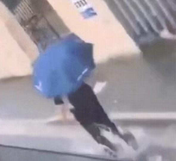 快乐如此简单!魔都男孩撑着伞在路上踩水蹦跳!
