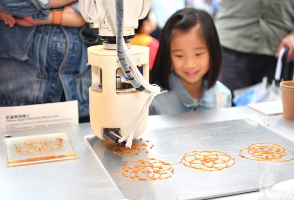 在这个脑洞大开的露天集市里 机器人用声音作糖画 用咖啡渣3D打印环保眼镜